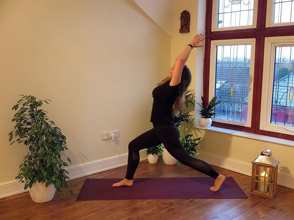 Woman on yoga mat holding yoga pose