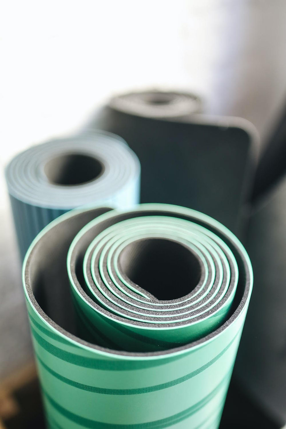 Detail of rolled-up yoga mats, standing on end