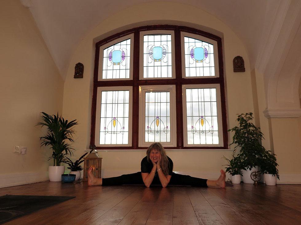 Woman sitting on yoga mat in studio
