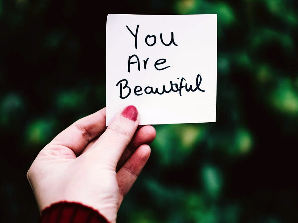 """Hand holding up small not with the words """"You are beautiful"""" written in black marker pen"""