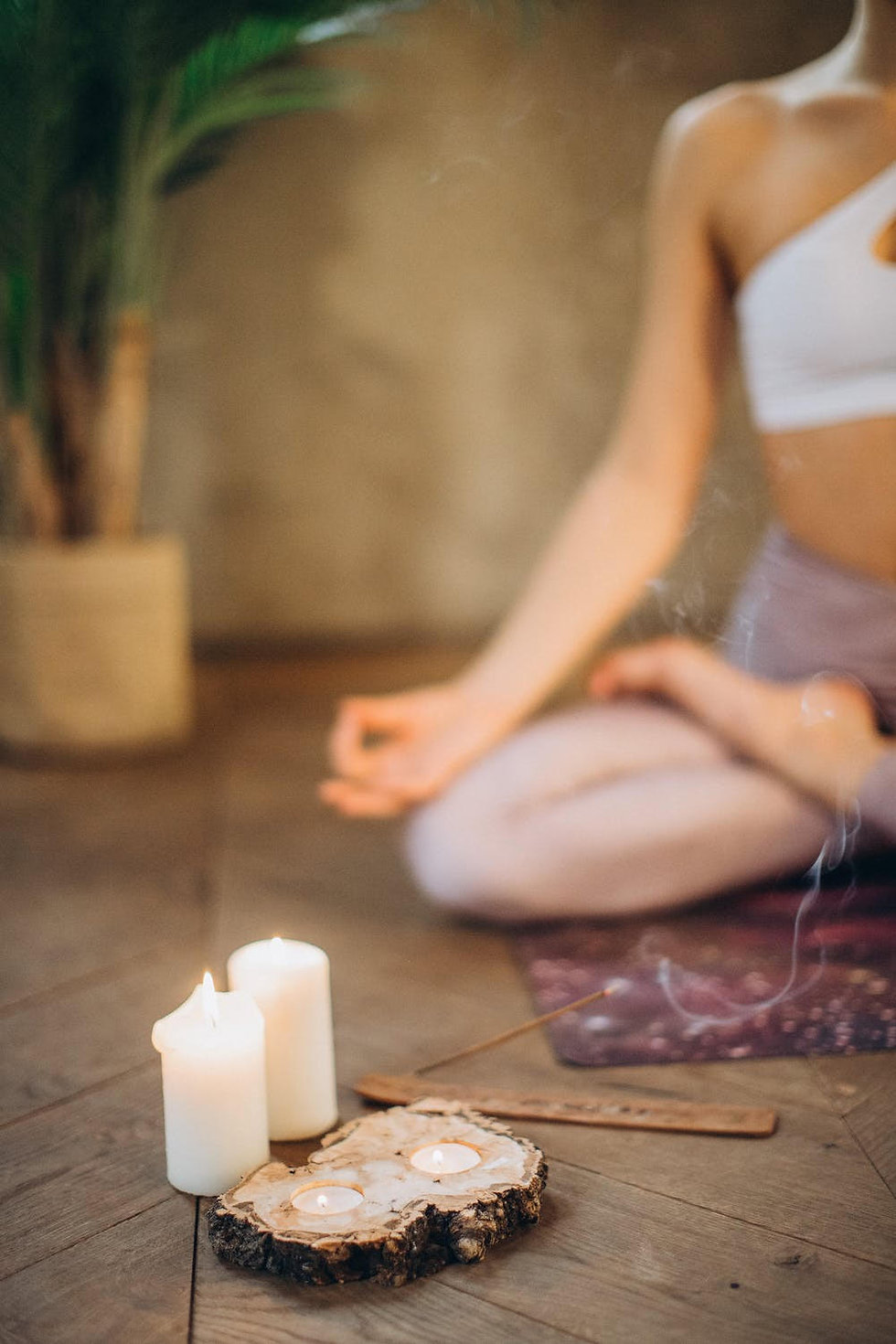 Detail of burning candles with yoga student sitting cross-legged in the background