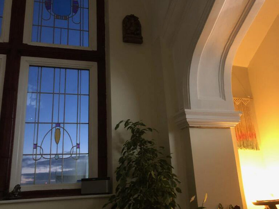The Yoga Bak Studio with warm lighting, and dusky evening sky though the window