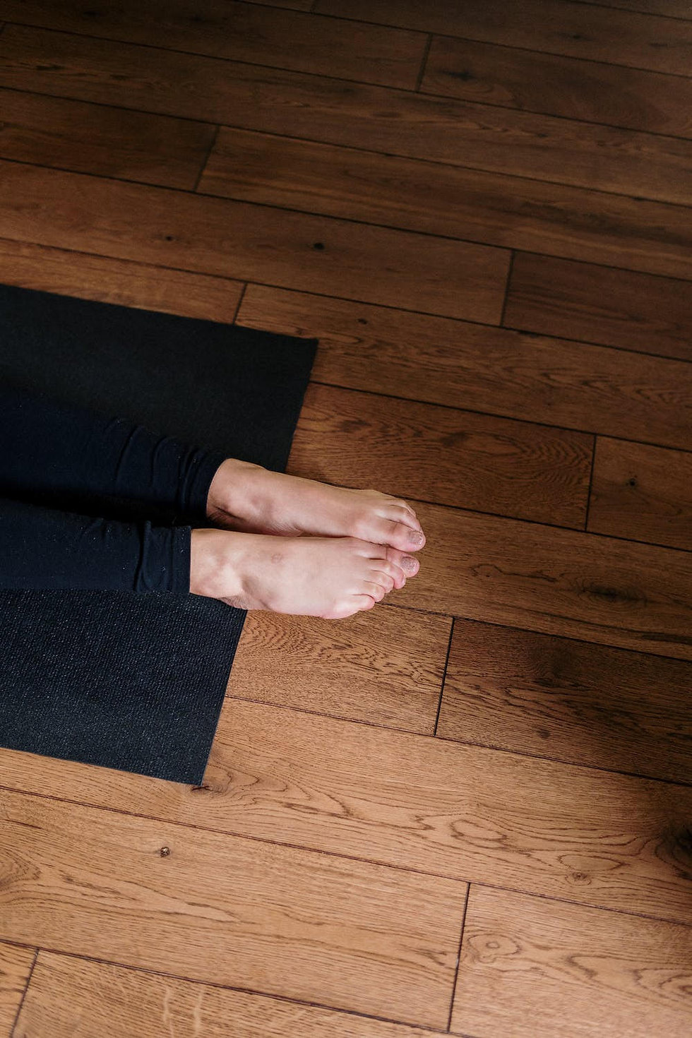 Woman lying down on  yoga mat, with bear feet extending off the end