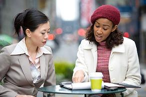 two women talking outdoors