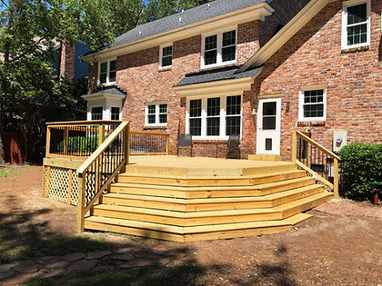 A treated wood deck, with multi-directional steps on a brick house.
