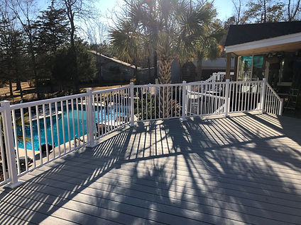A second story, composite deck overlooking an inground swimming pool