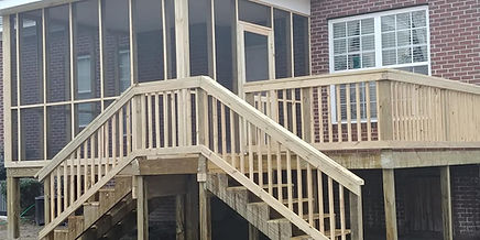 High rise wood deck, connected to a screend in porch with bi-directioal staircase steps.