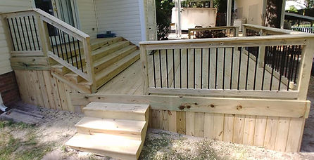 A traditinal wooden deck, with metal railing and eclosed bottom.