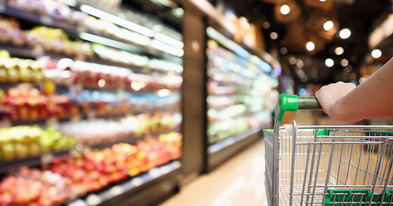 Blurred image of shopping cart with hand in grocery store aisle.