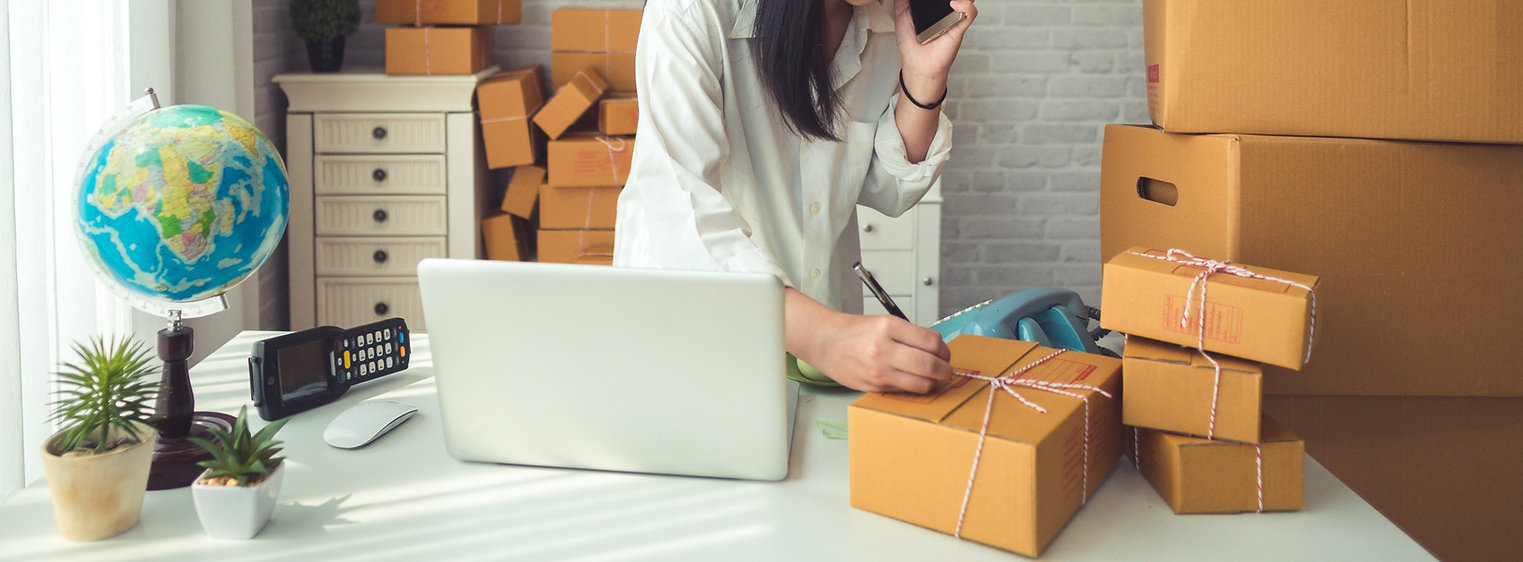 Image of adult on phone in front a computer while addressing a moving box with orange and green overlay.