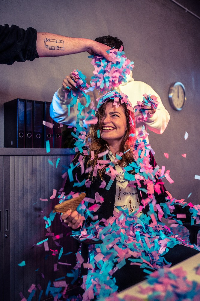 Young professional girl laughing as she is being covered with confetti