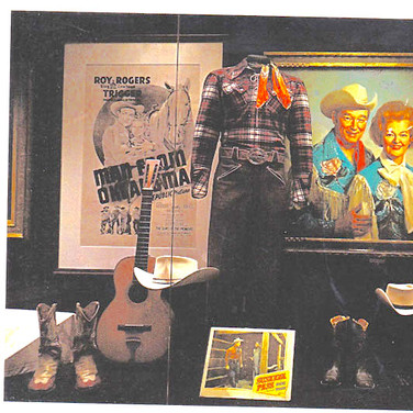 Roy Rogers and Dale Evans with Trigger's poster behind them