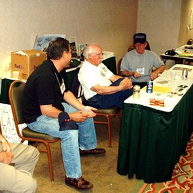 """Chick, Francis Gary Powers Jr.,  """"Pappy"""" Ppworth and Ed Morris at the desk""""Pappy"""" Papworth"""