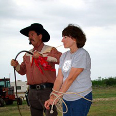 "Connie got all tied up and our cowboy is going to ""try"" to cut the straw from her mouth with his bull whip!"