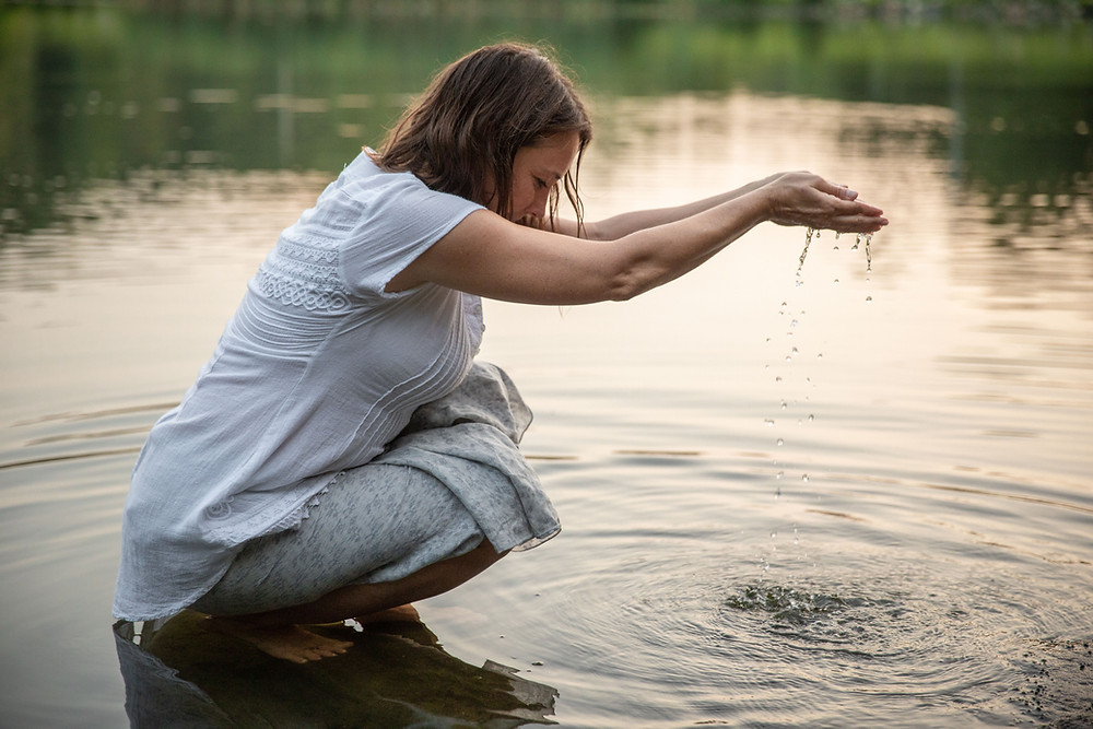 Lila squatted down in a shallow lake edge, with water flowing through her fingers