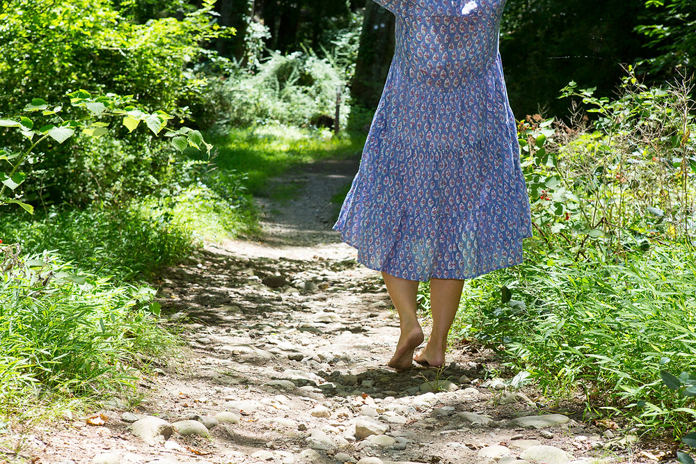 bare feet walking on a path within the forest.