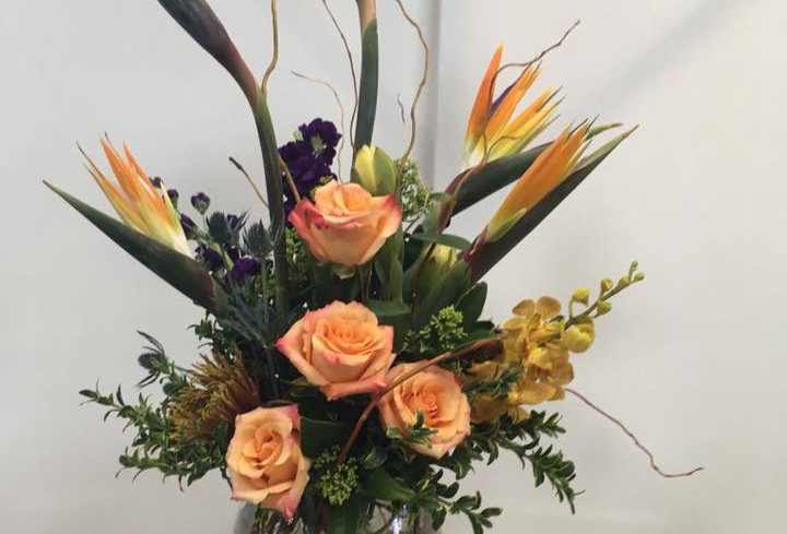 Birds of Paradise, Roses, Orchids, Lush Green + Curly WIllow. Flowers may vary based on seasonality