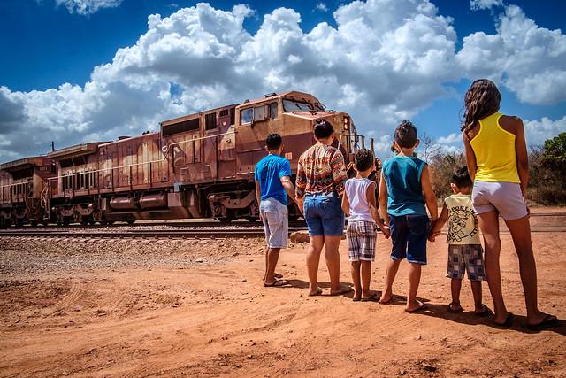 Família a espera que o trem, carregado de minério, passe para atravesar - Créditos: Felipe Larozza
