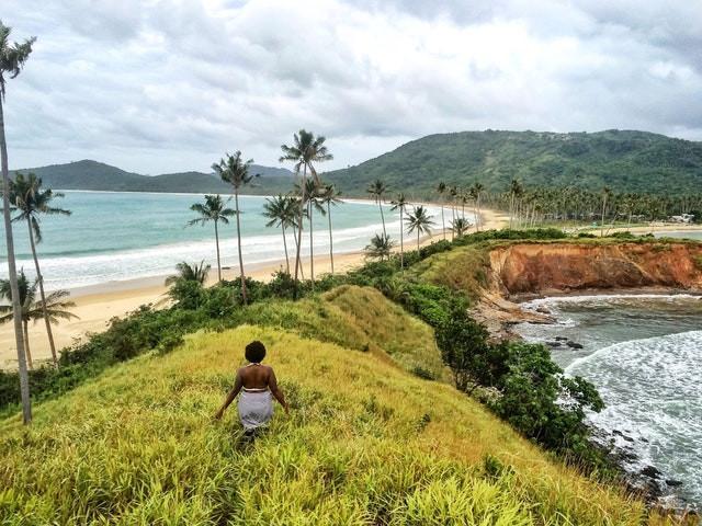 Black woman walking in paradise solo travel ocean beach palm trees