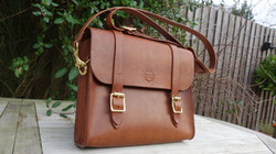 Chestnut satchel with rust stitching, and cast brass buckles