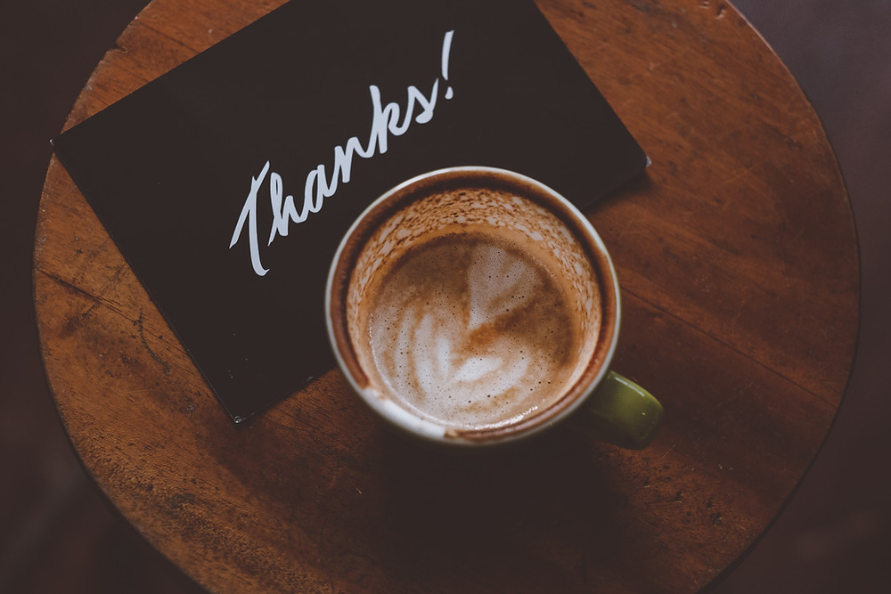 a half drank latte sits on a black thank you note on a brown wooden table