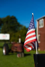 American flag in the foreground with an antique tractor in the background