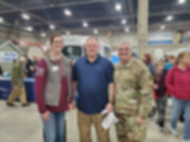 A woman and man in civilian clothes with a NationalGuard General at the PA Farm Show