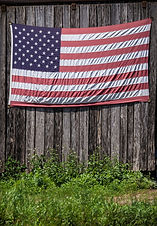 An Amerian flag hung on the side of a barn
