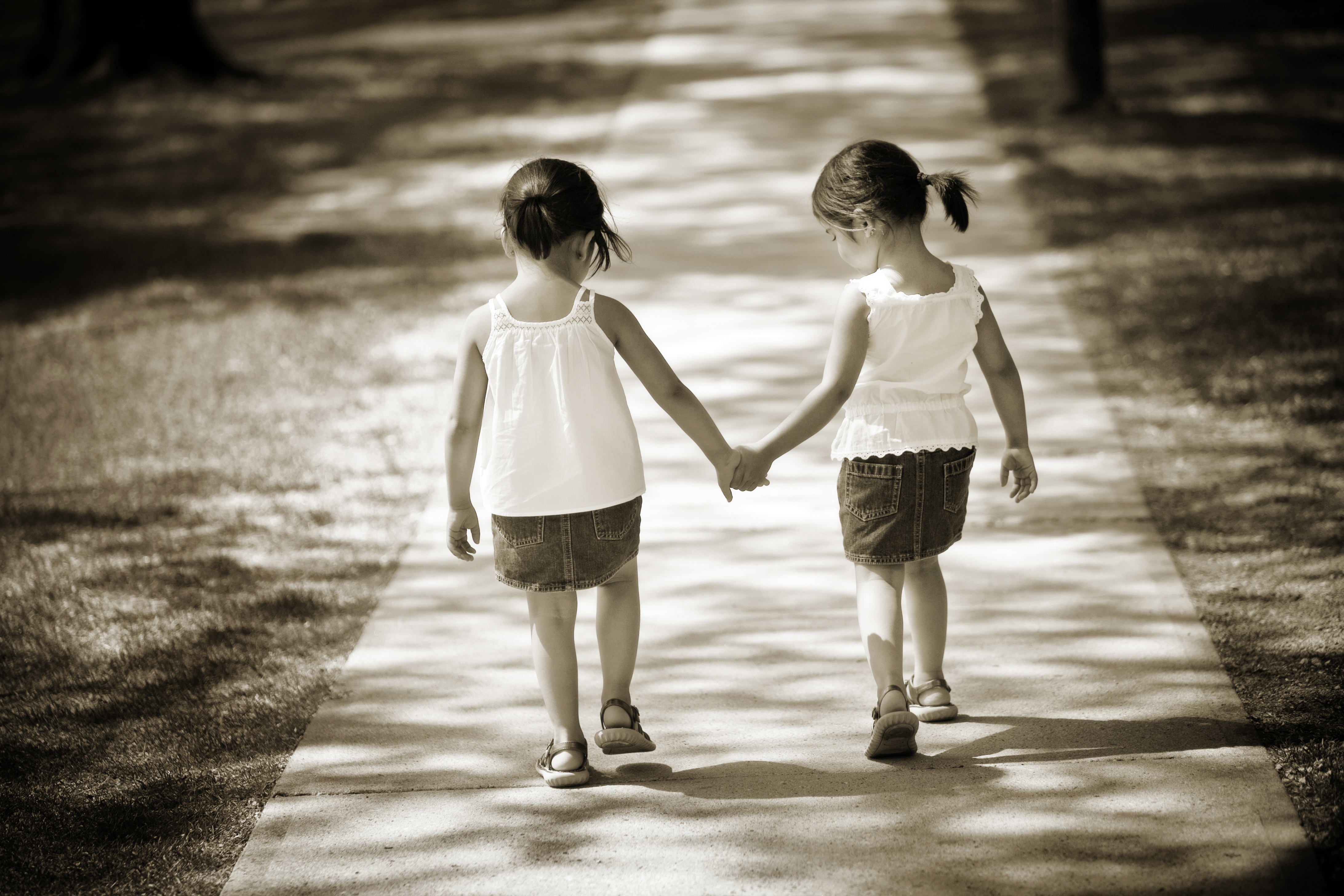 Young twin sisters holding hands walking away down a path