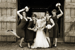 Bride and bridesmaids in a fun pose in front of a rustic building
