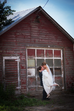 Groom picking up bride as they embrace in frount of old rustic barn