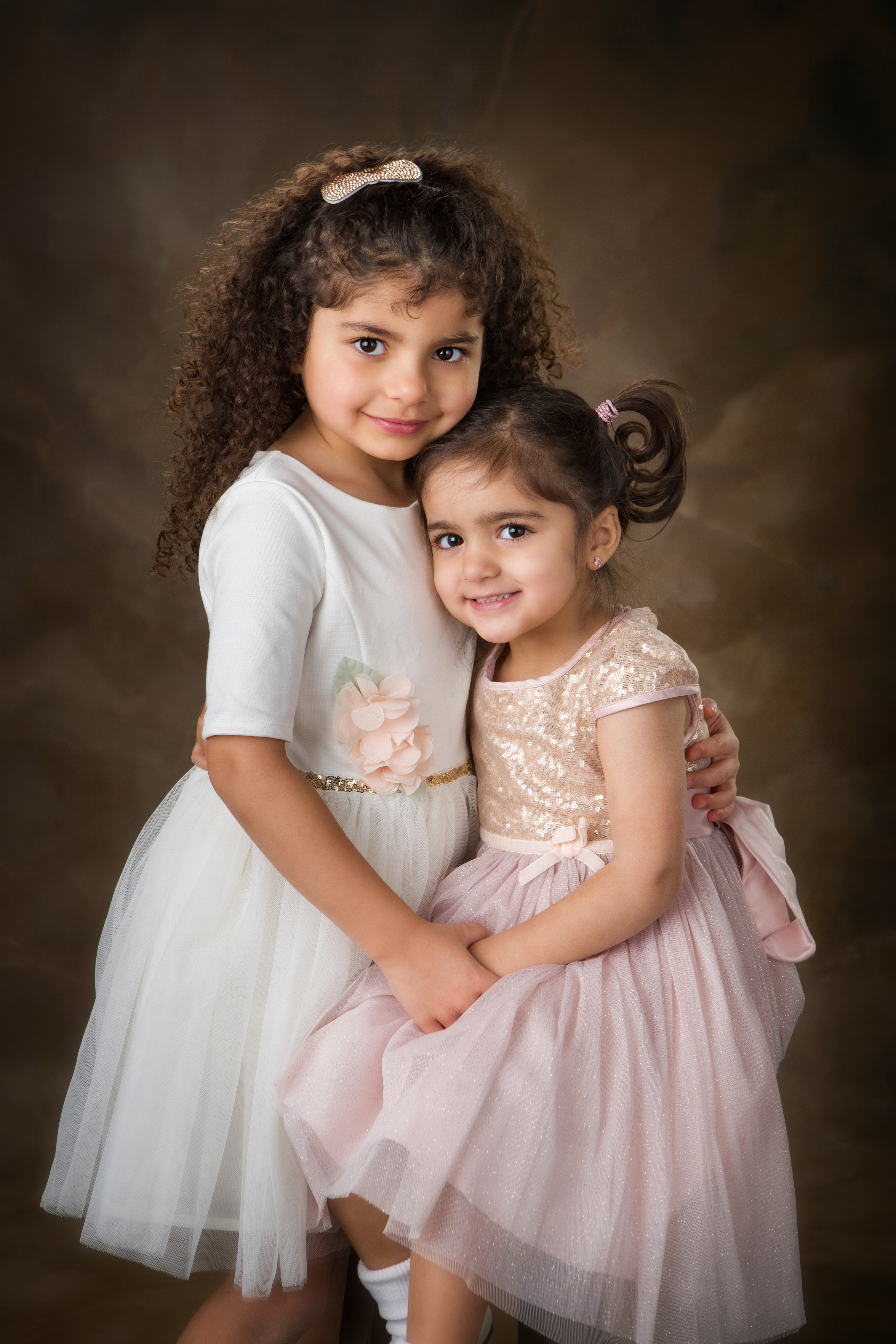 Young sisters in white and pink dresses with their arms around each other