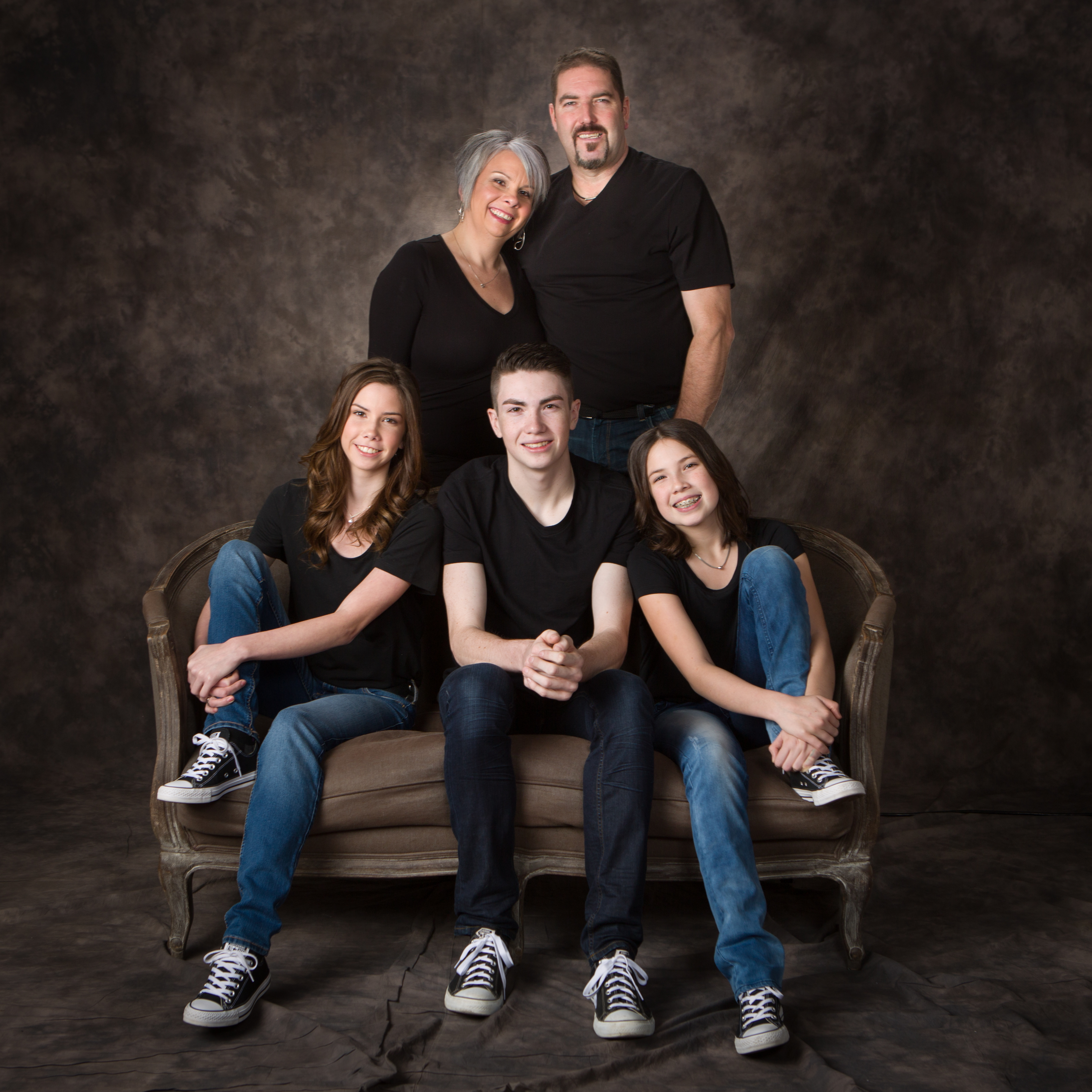 Family of five posing if front of a studio background