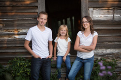 Three school aged siblings stand together in front of an old barn