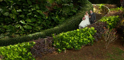 Bride and father walking down tropical pathway together
