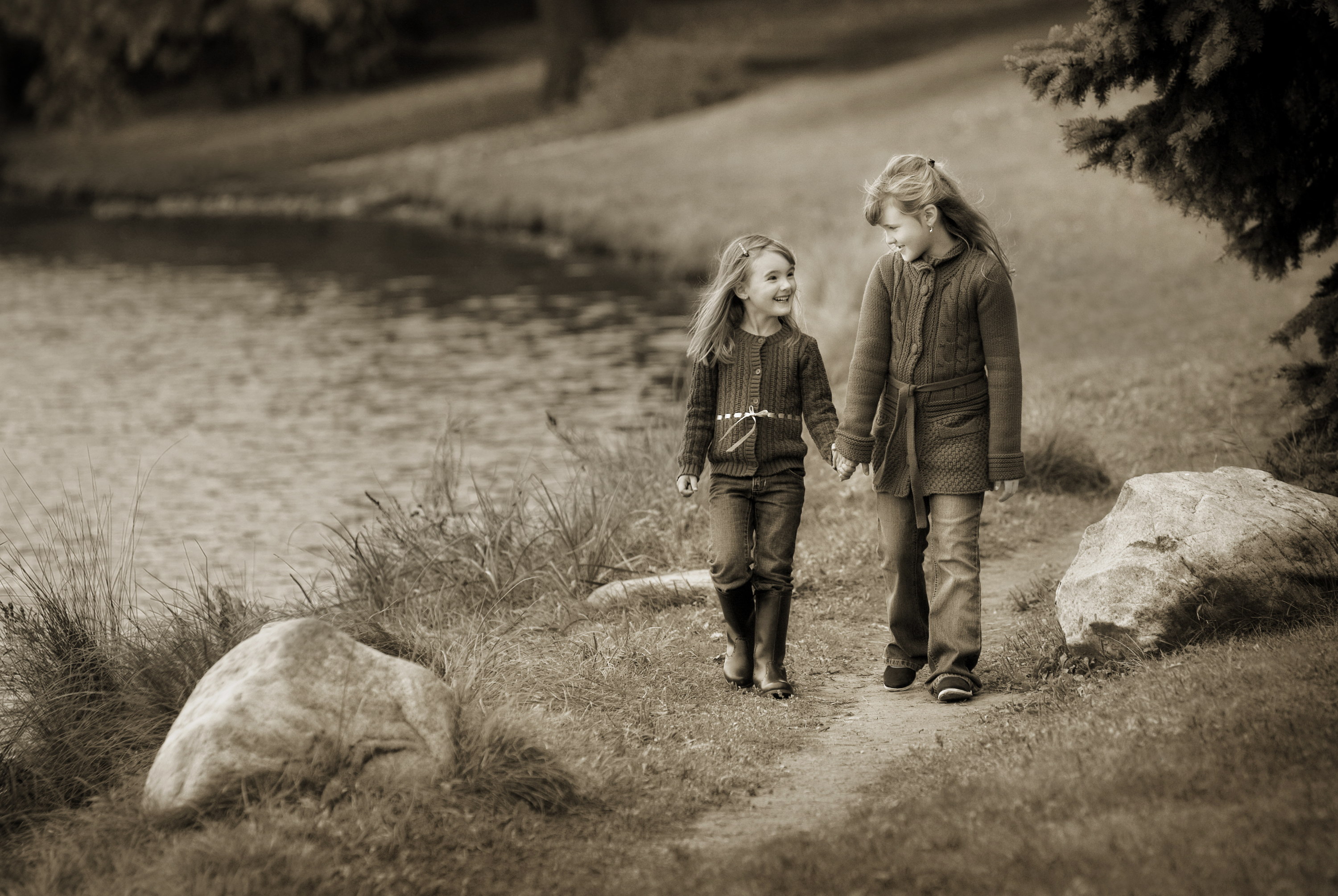 Two young sisters walking hand in hand looking at each other smiling