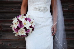 Close up of bride standing in front of rustic barn holding purple and white bridal bouquet