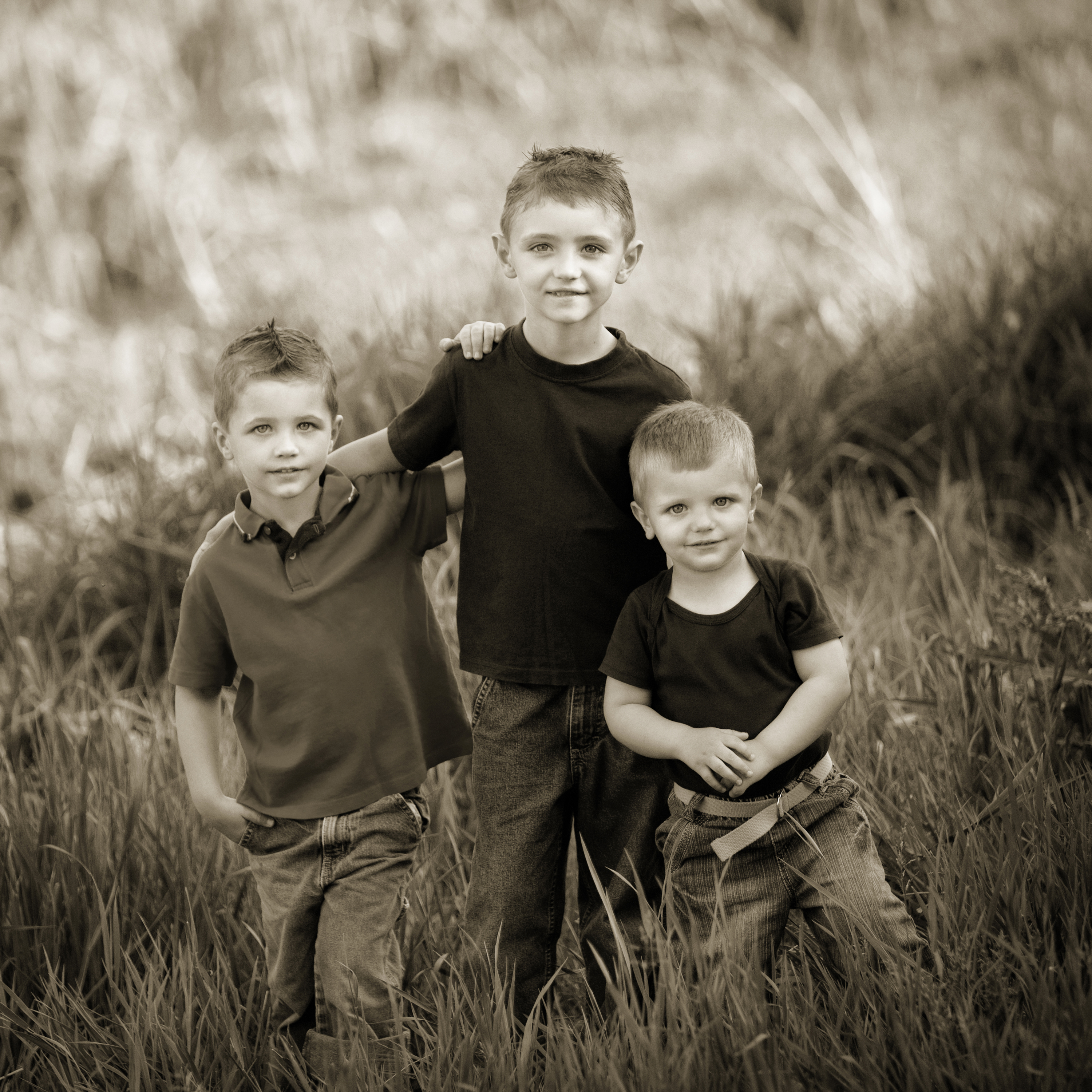 Three young brothers standing in the tall grass