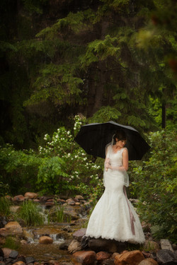 Bride standing in forest setting holding a black umbrella