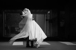 Groom twirling bride around as they kiss