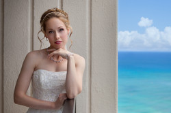 Bride standing on hotel balcony in Hawaii with ocean in background