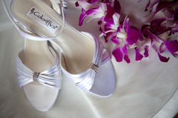 White satin shoes with purple orchid lei