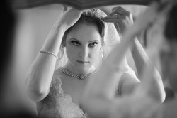 Bride looking into mirror as she adjusts her veil