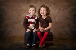Two cute smiling young siblings sitting on an old wooden trunk in front of a brown background