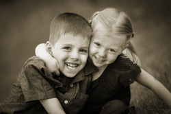 Young girl playfully wrapping her arm around her brother
