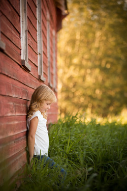 Young girl in white shirt looking down while leaning against an old red barn