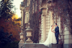 Bride and groom standing in front of old university building looking at each other