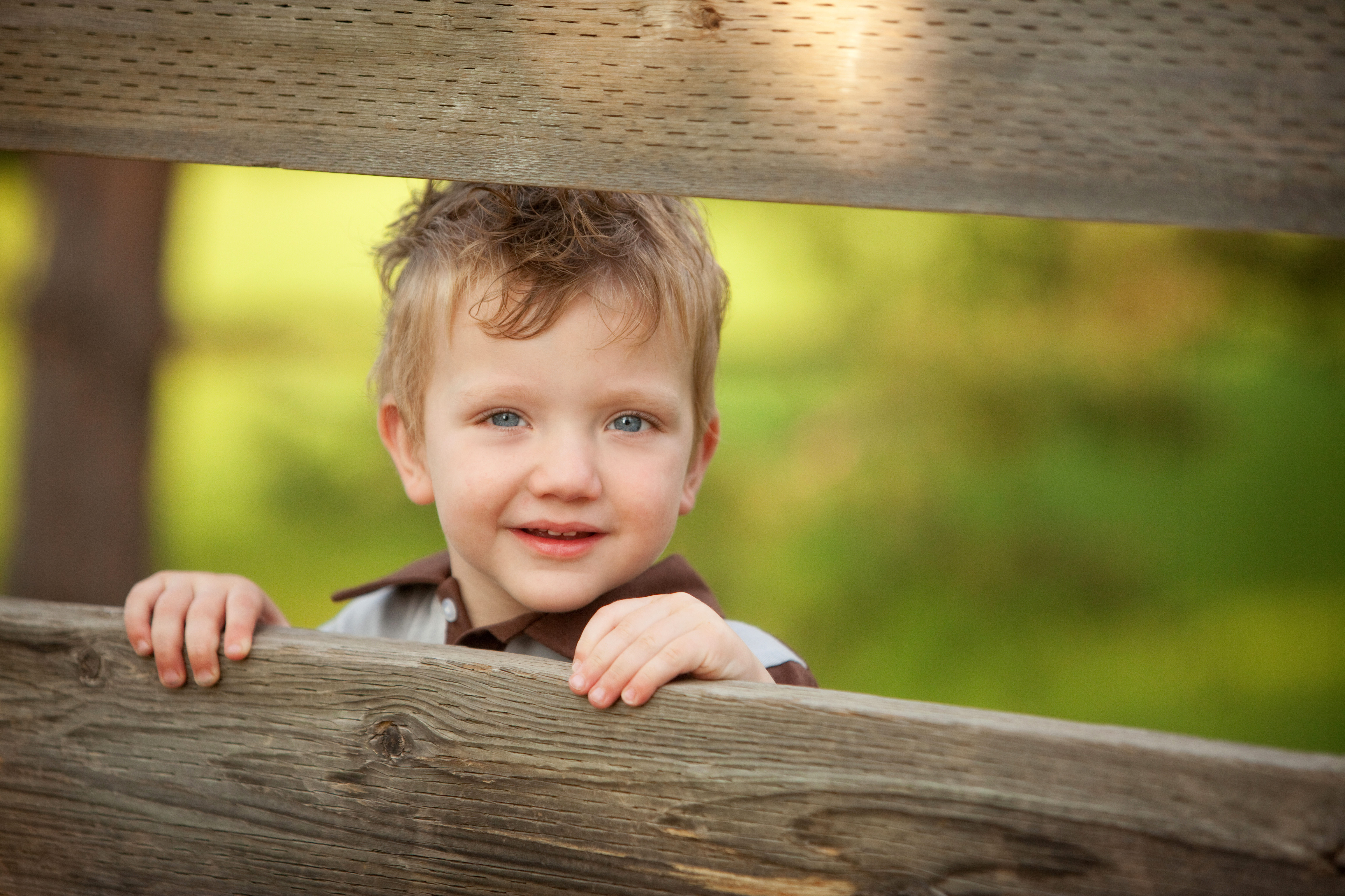 Smiling toddler looking through a wooden fence