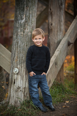 Young smiling boy with his hands in his pockets standing near rustic wooden bridge structure
