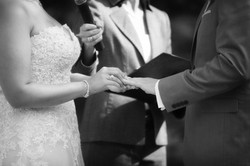Close up of bride placing ring on groom's finger